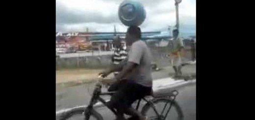 He balance a propane tank on his heads like a boss while riding in the bicycle